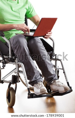 Young man on wheelchair working on laptop - stock photo