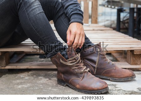 Young man on wood floor tying shoelaces on boots. A man wearing in a black shirt, black jeans and brown leather boots. - stock photo
