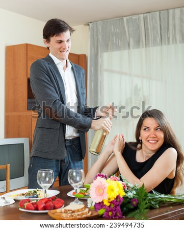 Young man opening bottle of champagne or sparkling wine - stock photo
