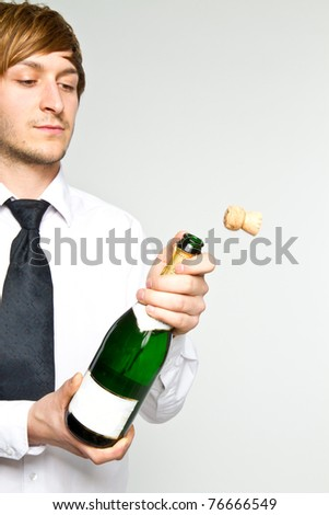young man opens sparkling wine - stock photo