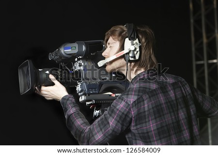 Young man operating a Television Camera in a TV Studio. - stock photo