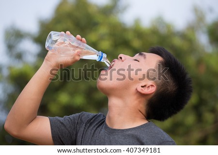 young man or teenager drinking water from plastic bottle