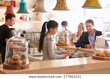 Young man ordering at the counter in a cafe - stock photo