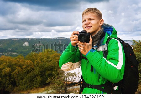 Young man outdoor photographer in mountain landscape - stock photo