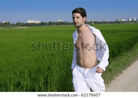 Young man outdoor running in a green rice field meadow