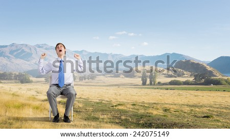 Young man outdoors sitting in chair and yawning - stock photo