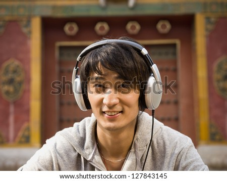 Young man outdoors with headphones smiling