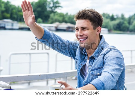Young man outside by the river  - stock photo
