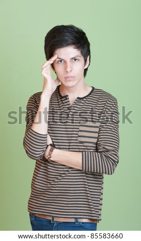 Young man over green background holds his head - stock photo