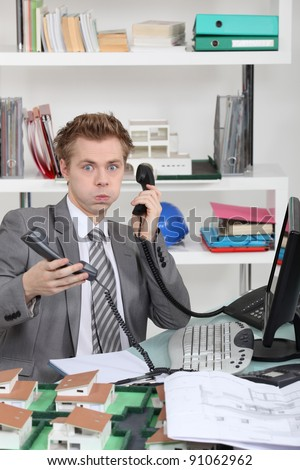 young man overwhelmed with phone calls - stock photo