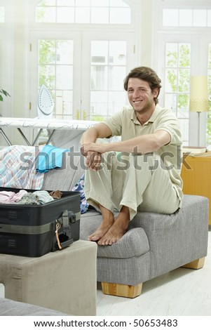 Young man packing for vacation. Sitting on couch beside full suitcase, smiling.