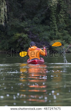 Young man paddling hard the kayak with lots of splashes.