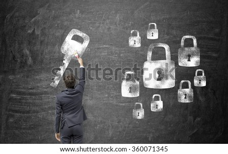 Young man painting a key to the locks on the blackboard with a brush. Black background. Back view. Concept of finding a solution. - stock photo