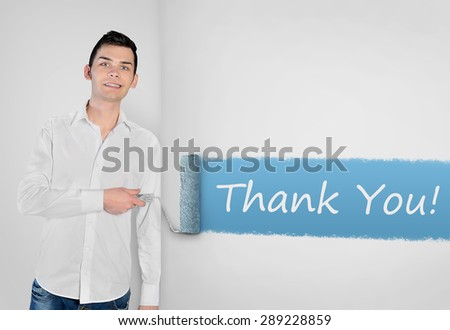 Young man painting Thank you word on wall - stock photo