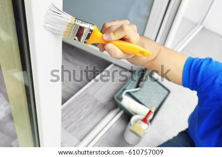 young man painting window at home closeup