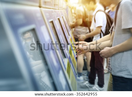 young man paying at ticket machine in a metro station - stock photo