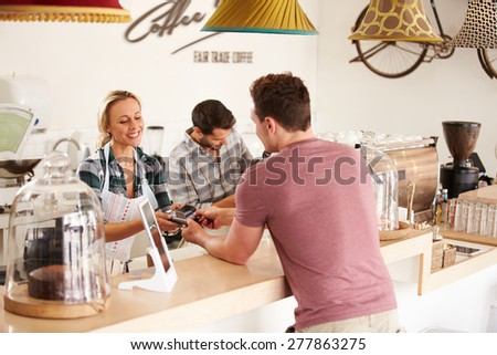 Young man paying for his order in a cafe - stock photo