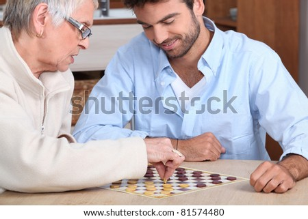 Young man paying game with old lady - stock photo
