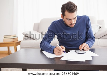 Young man paying his bills at home in the living room - stock photo