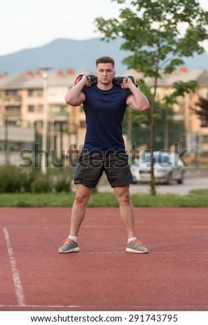 Young Man Performing Bag Squat Exercise Outdoor