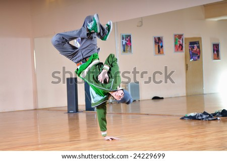 young man performing break dance in dance studio - stock photo