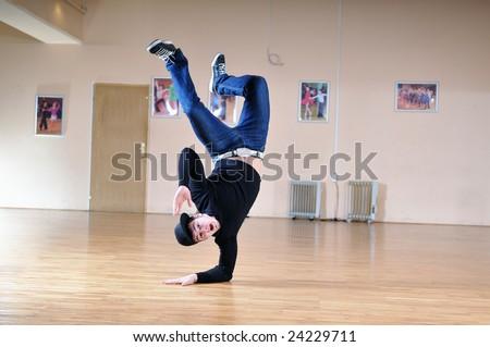 young man performing break dance in dance studio - stock photo