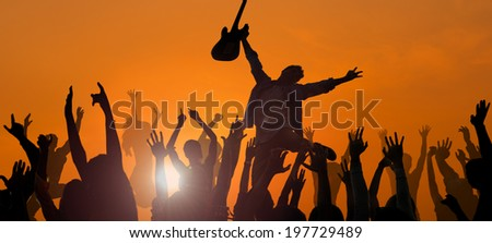 Young Man Performing with a Guitar in Front of the Crowd - stock photo