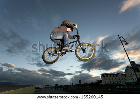 Young man performs stunts during sunset at the street. - stock photo