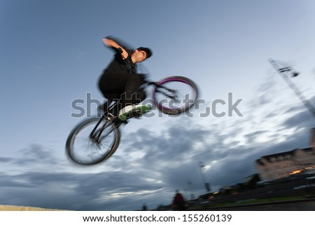 Young man performs stunts during sunset at the street. Blurred motion.