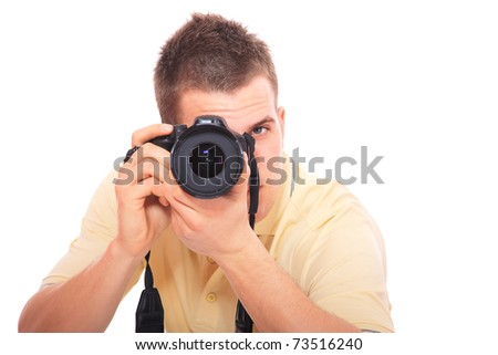 young man photographer taking pictures with his DSLR - stock photo