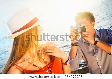 Young man photographing a beautiful girl - stock photo