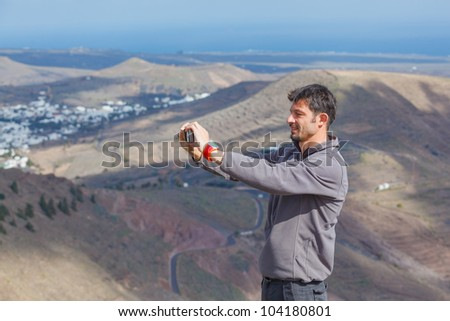 Young man photographing a beautiful mountain view - stock photo