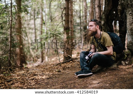 Young man photographing in forest on medium format camera