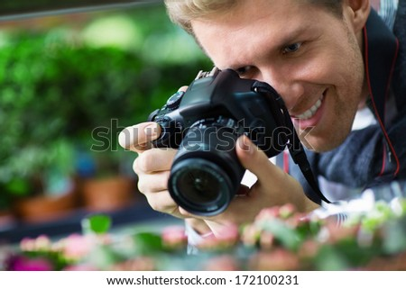 Young man photographs the flowers - stock photo