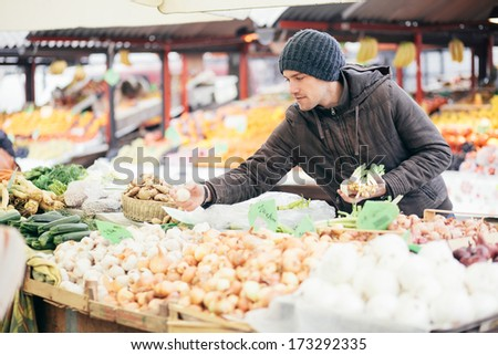 Young man picking vegetables at farmers's market - stock photo