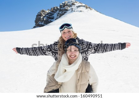 Young man piggybacking cheerful woman against snow covered hill and clear blue sky - stock photo