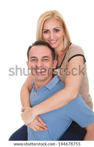 Young Man Piggybacking Woman Over White Background - stock photo