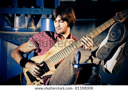 young man play bass guitar at industrial area by the river at sunset - stock photo