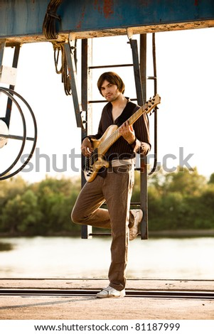young man play bass guitar at industrial area by the river at sunset, full body shot - stock photo