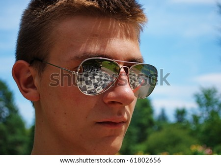 Young man play chess in park.Board is reflected in his sunglasses