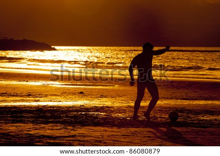 young man play football at sunset in the beach - stock photo