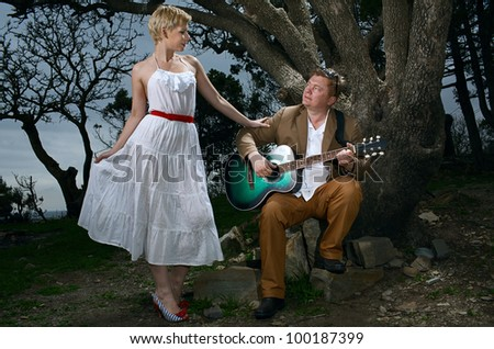 young man play guitar for woman - stock photo