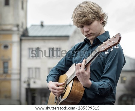 Young man play on the acoustic guitar on the street - stock photo