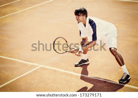 young man play tennis outdoor on orange tennis court  - stock photo