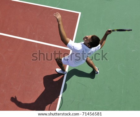 young man play tennis outdoor on orange tennis court at early morning - stock photo