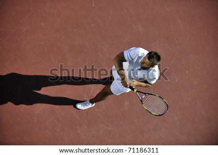 young man play tennis outdoor on orange tennis field at early morning - stock photo