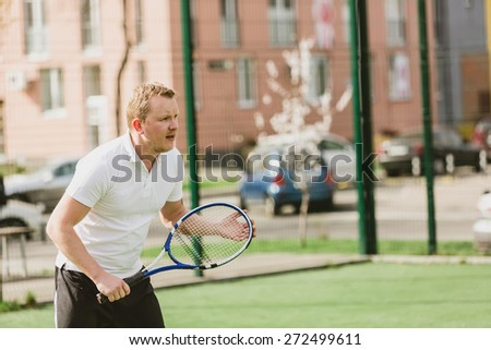 young man play tennis outdoor on tennis field at early morning - stock photo