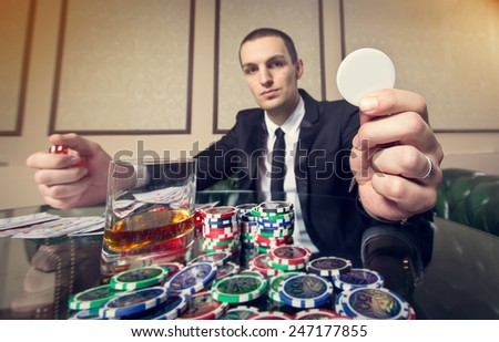 Young man player. Playing cards. Game table, chips, cubes, whiskey, alcohol, gambling, game, casino, gambling house - concept about men's entertainment. Spend time playing cards for money. Gambling. - stock photo