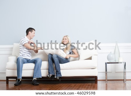 Young man playfully hits a young woman with a pillow on the sofa. Horizontal shot. - stock photo
