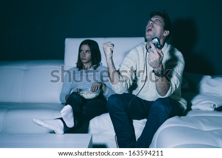 Young man playing a game at home his girlfriend is annoyed - stock photo